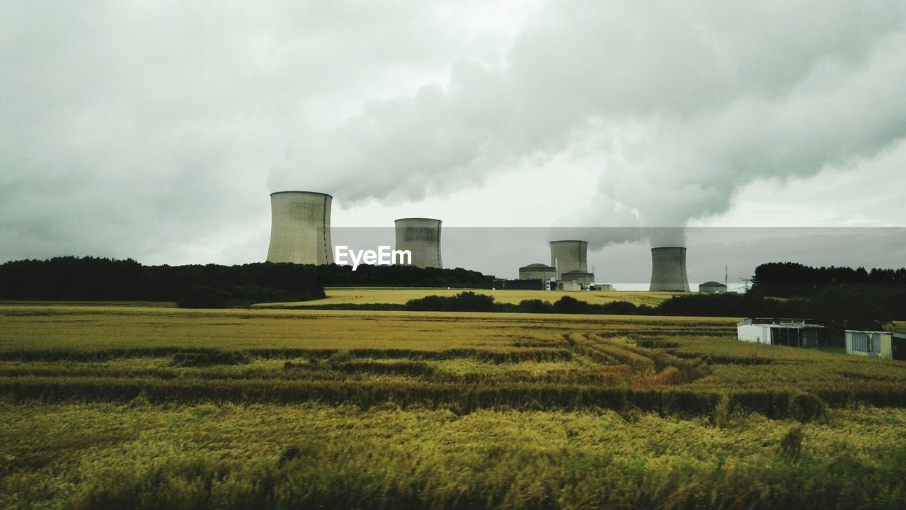 field, industry, cooling tower, smoke stack, factory, air pollution, built structure, agriculture, day, smoke - physical structure, landscape, no people, sky, outdoors, fuel and power generation, architecture, power station, rural scene, nature, building exterior