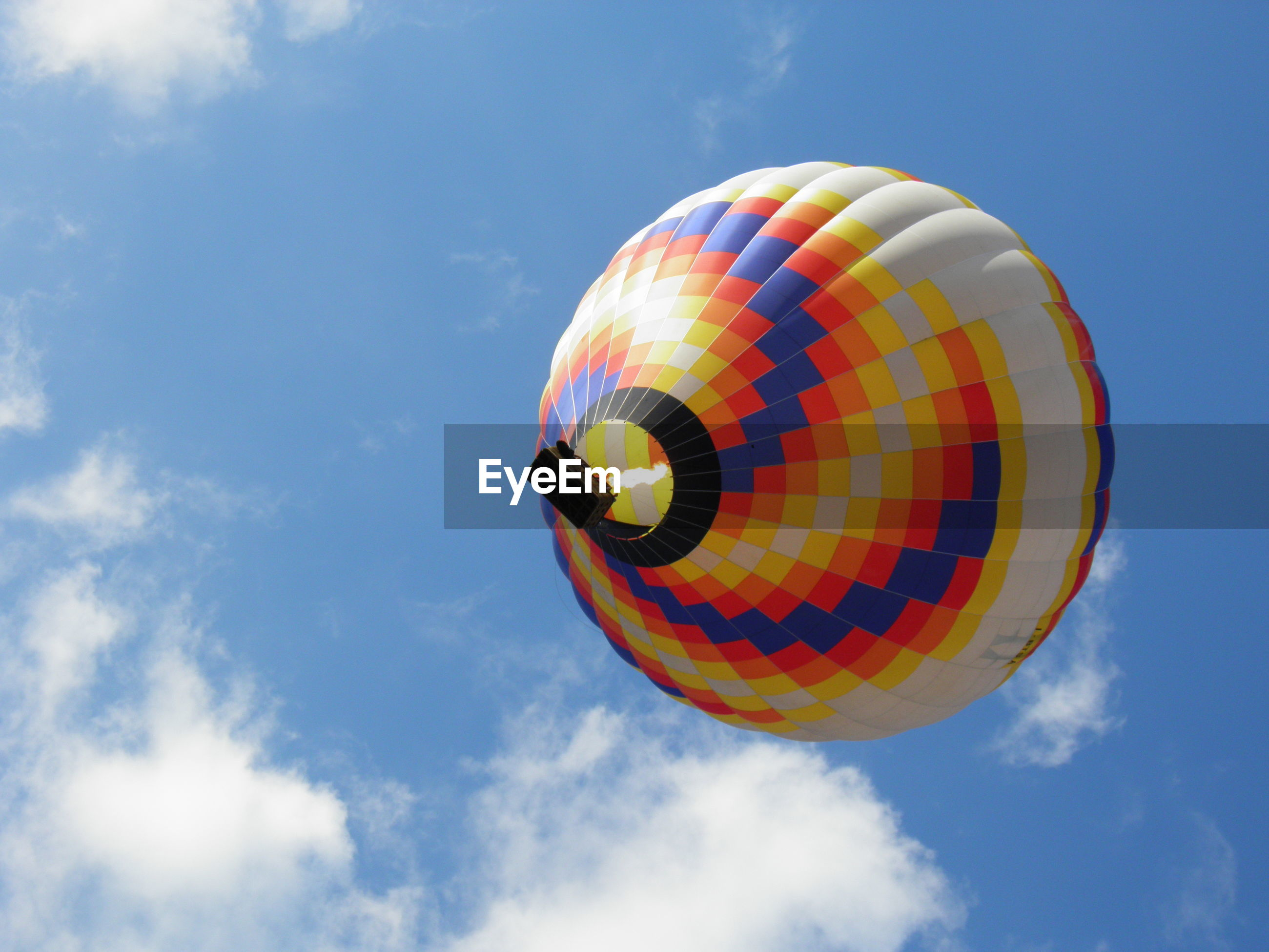 Low angle view of hot air balloon flying in blue sky
