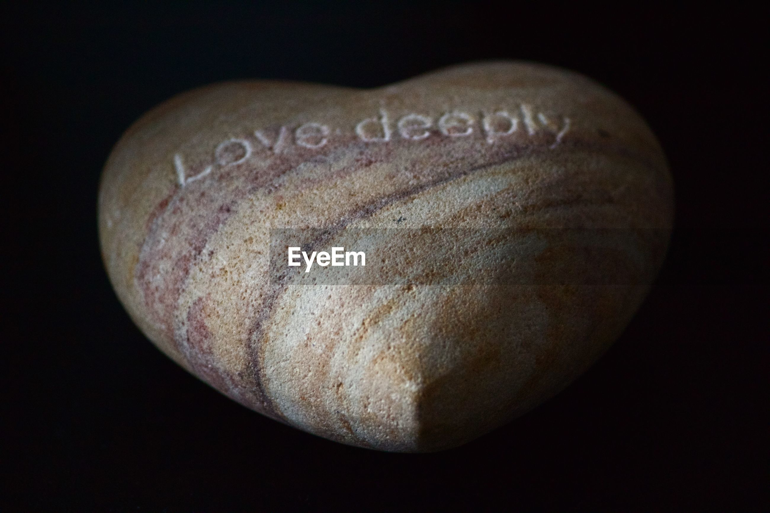 Text on heart shape stone against black background