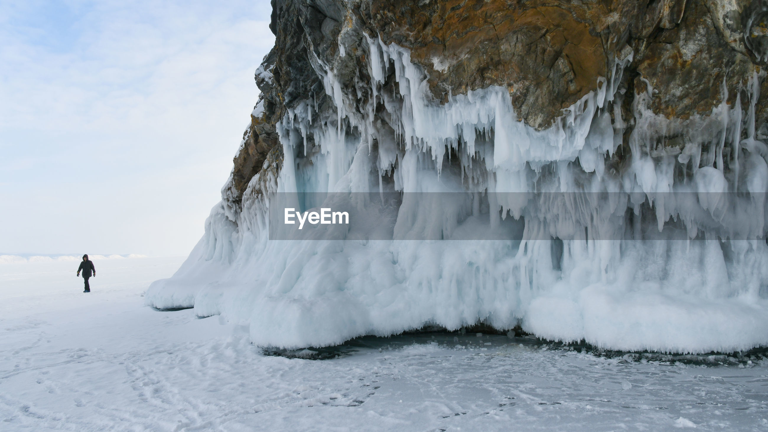 PANORAMIC SHOT OF PERSON STANDING ON FROZEN SEA