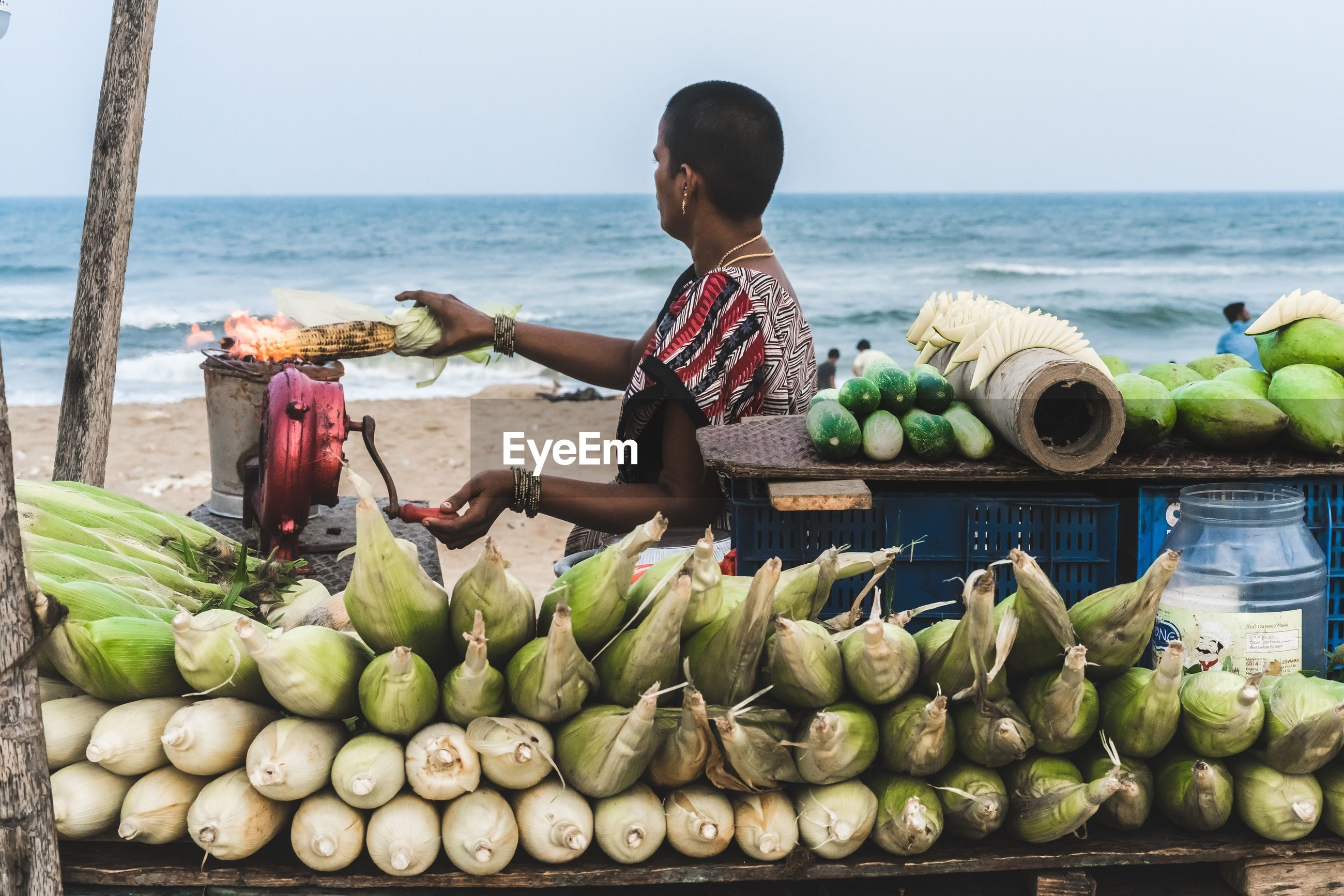 WOMAN AT MARKET STALL BY BEACH