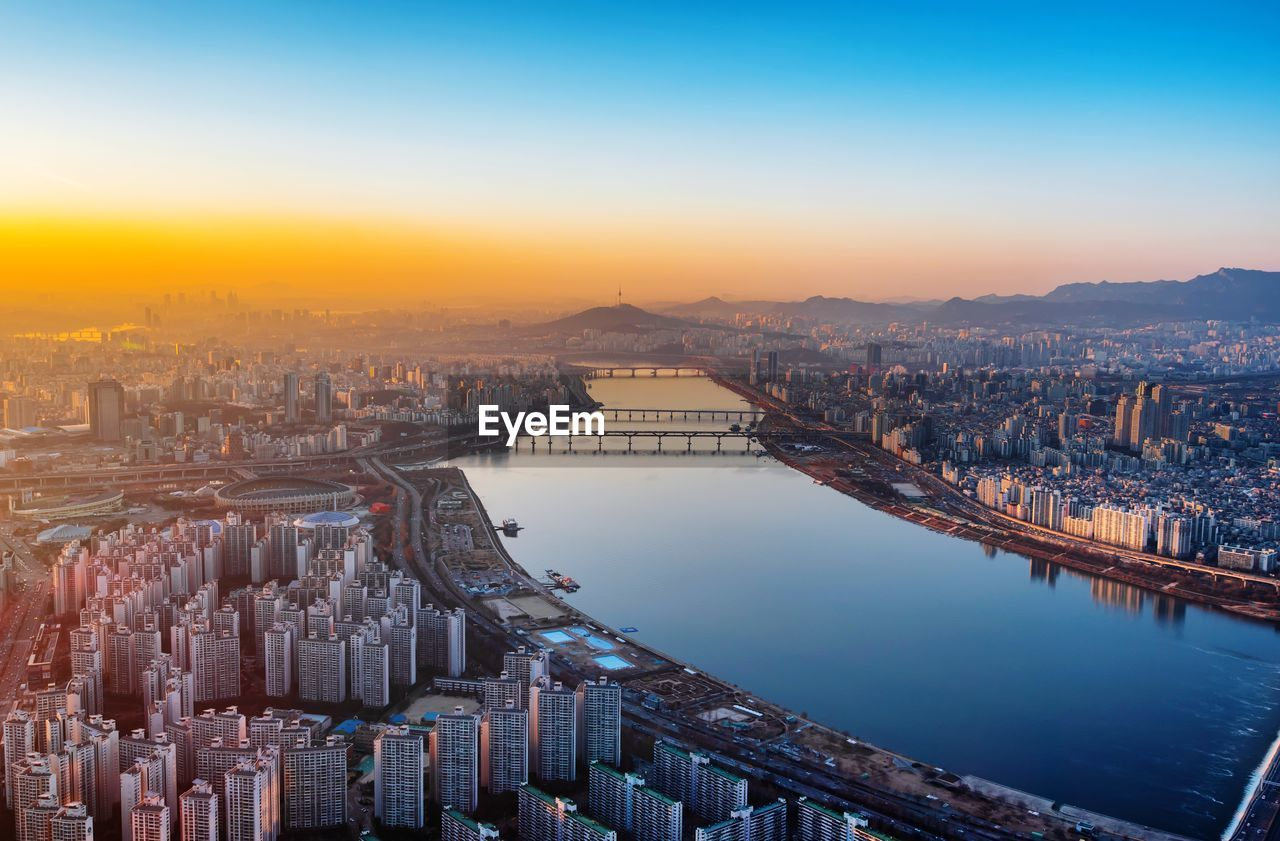 Aerial view of river amidst buildings in city during sunrise