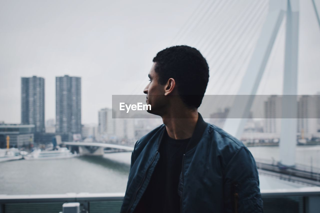 Young Man Looking At City While Standing Against Bridge