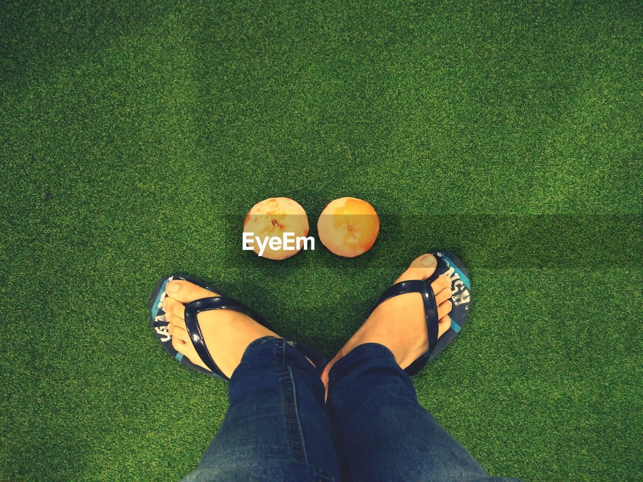 grass, one person, low section, healthy eating, human leg, green color, high angle view, directly above, jeans, real people, casual clothing, fruit, leisure activity, human body part, standing, lifestyles, day, freshness, women, men, food, outdoors, people, adult