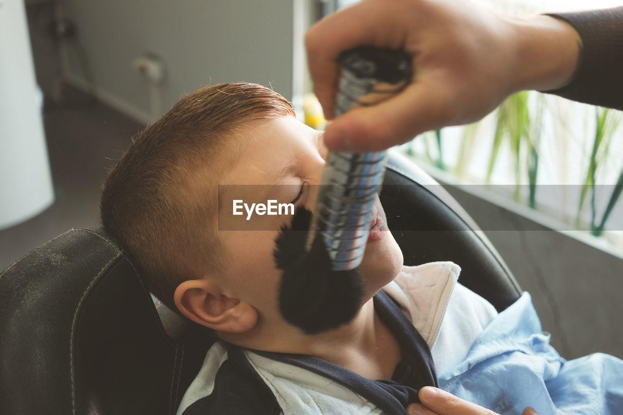Cropped image of man brushing on boy face at hair salon