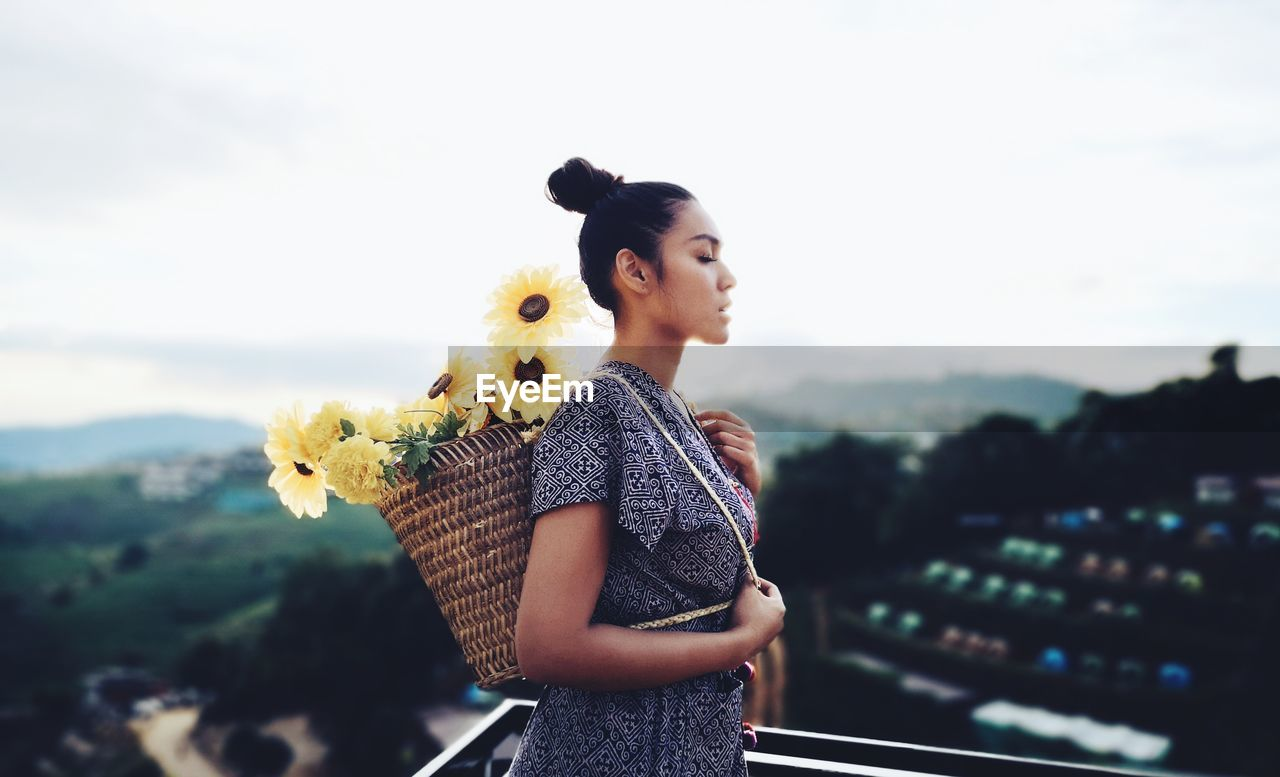 Woman carrying flowers in basket while standing at terrace