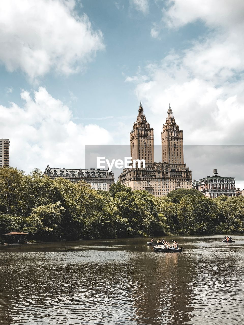 Buildings by river against cloudy sky