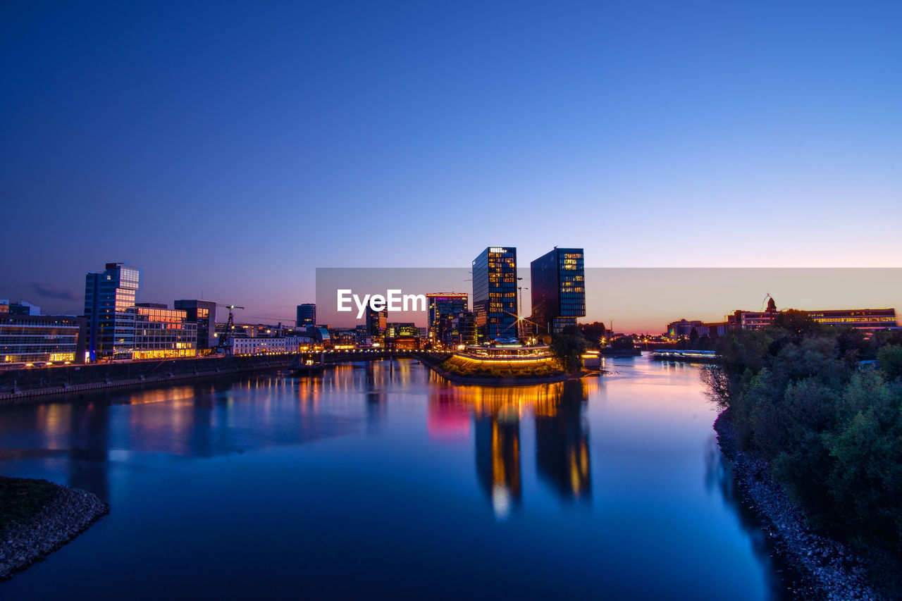 sky, building exterior, architecture, built structure, water, reflection, city, illuminated, waterfront, nature, clear sky, building, river, no people, sunset, blue, dusk, copy space, landscape, office building exterior, skyscraper, cityscape, outdoors