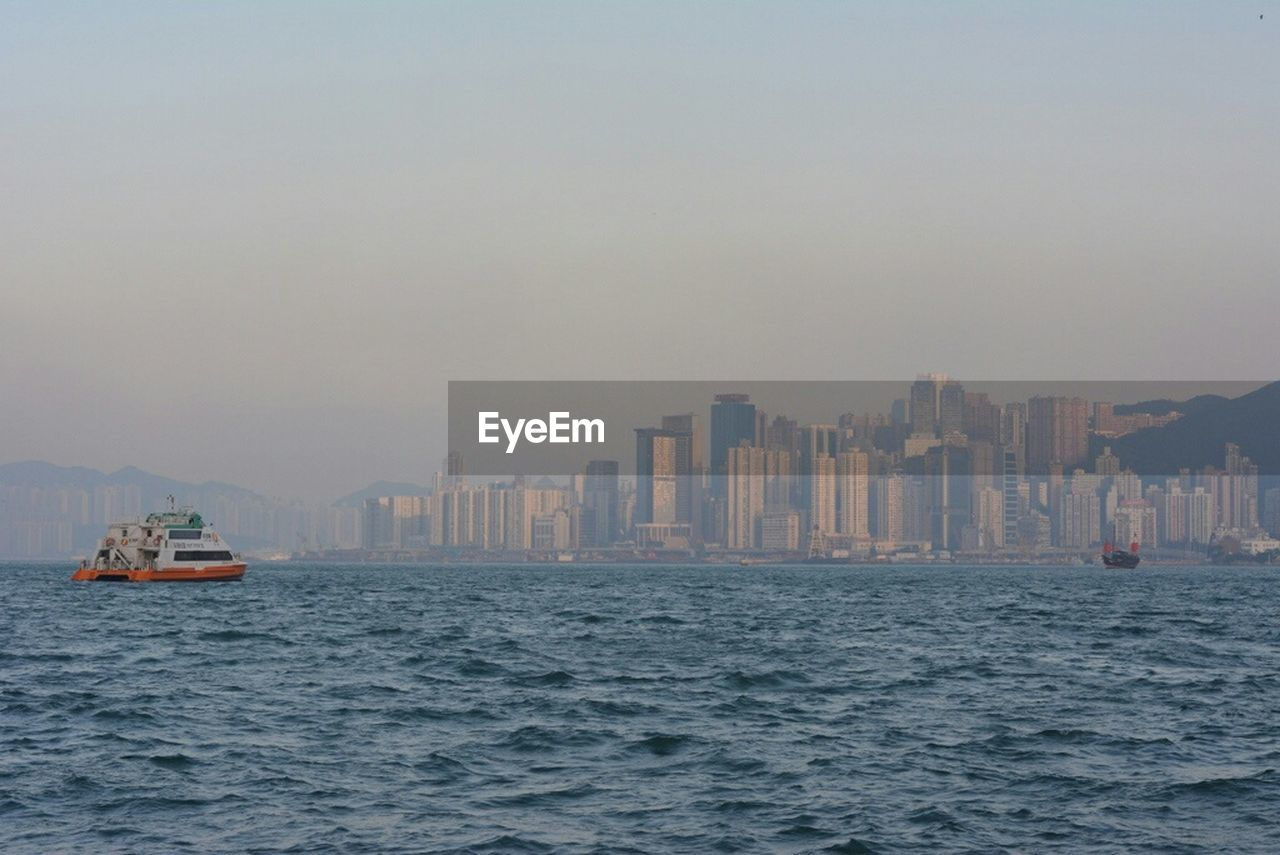 Yacht Sailing In Sea Against Buildings In City