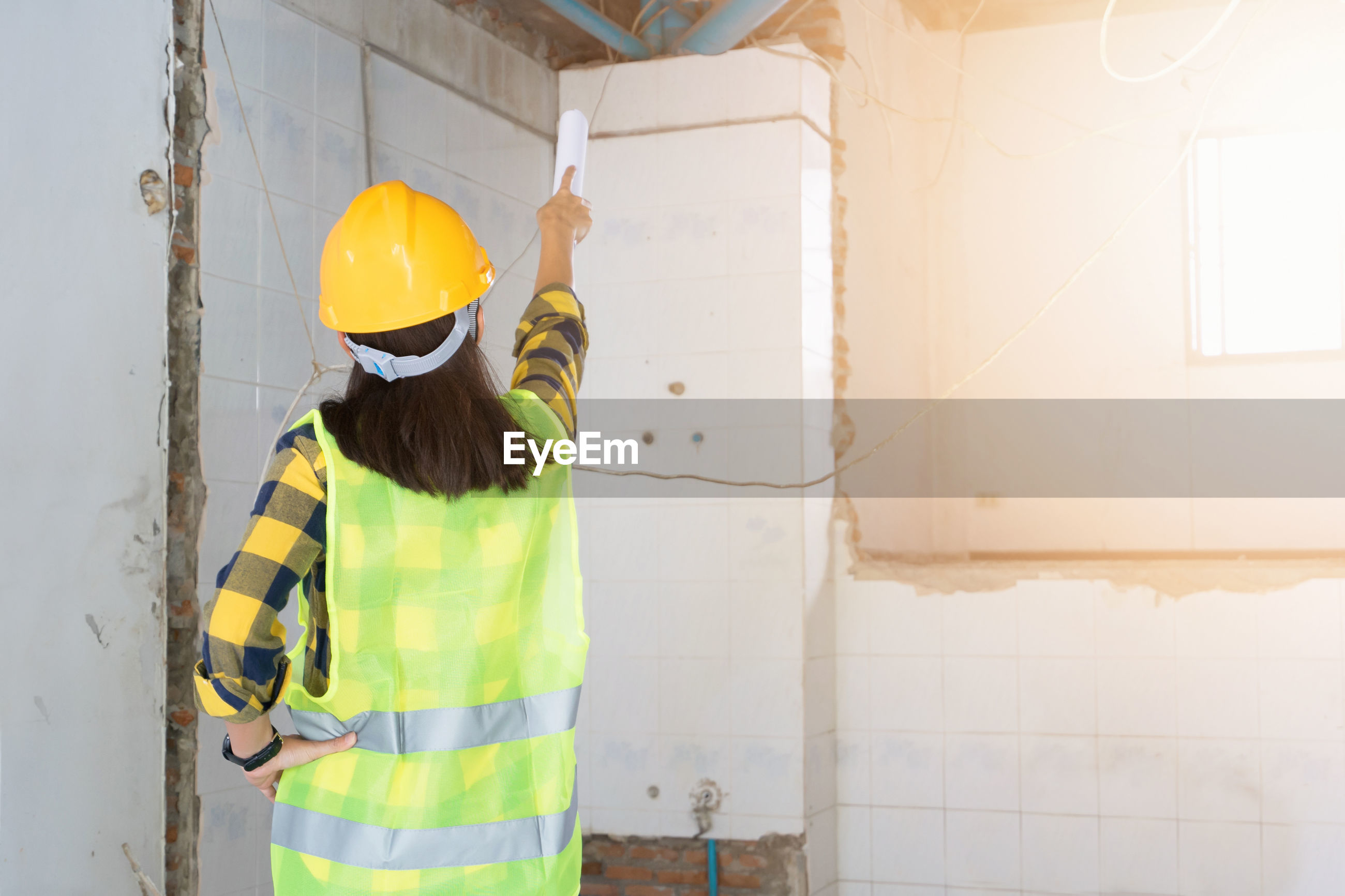 Engineer pointing against wall at home