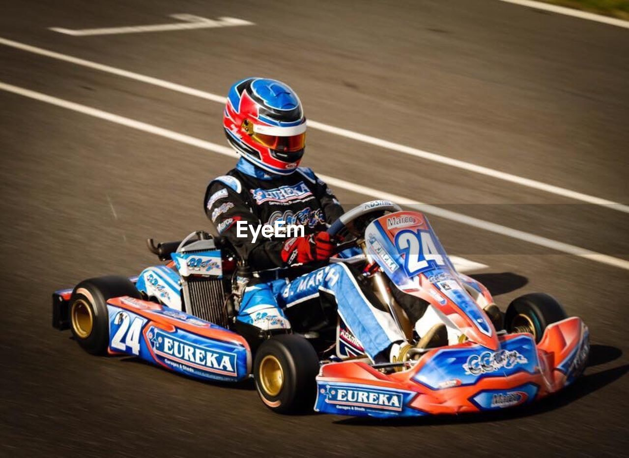 sports race, motorsport, speed, racecar, crash helmet, auto racing, sports track, helmet, sport, competition, sports clothing, sports helmet, competitive sport, formula one racing, motion, headwear, toy car, real people, lifestyles, adventure, outdoors, multi colored, one person, day, finish line, people