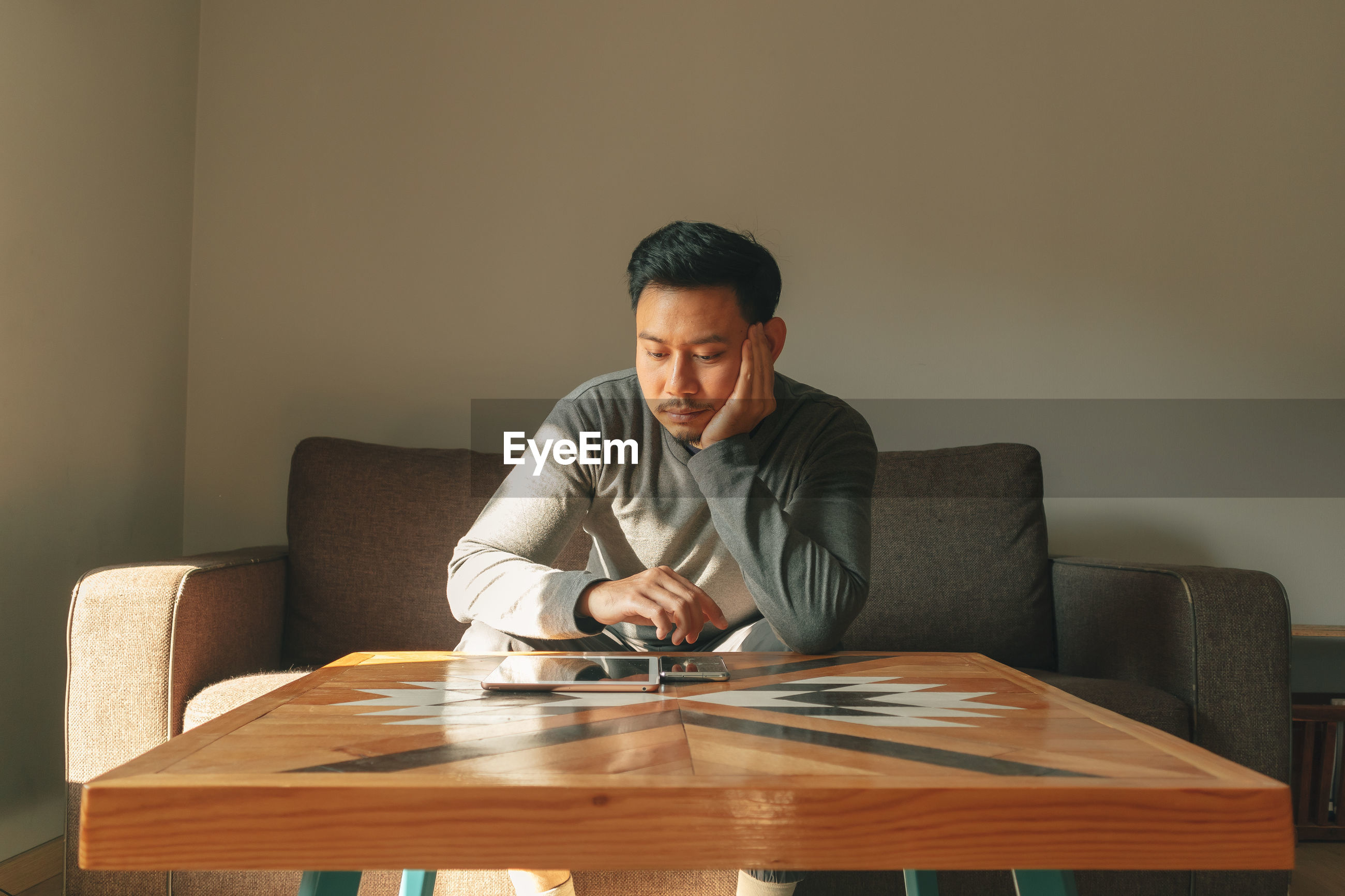 Thoughtful man with digital tablet sitting on sofa at home