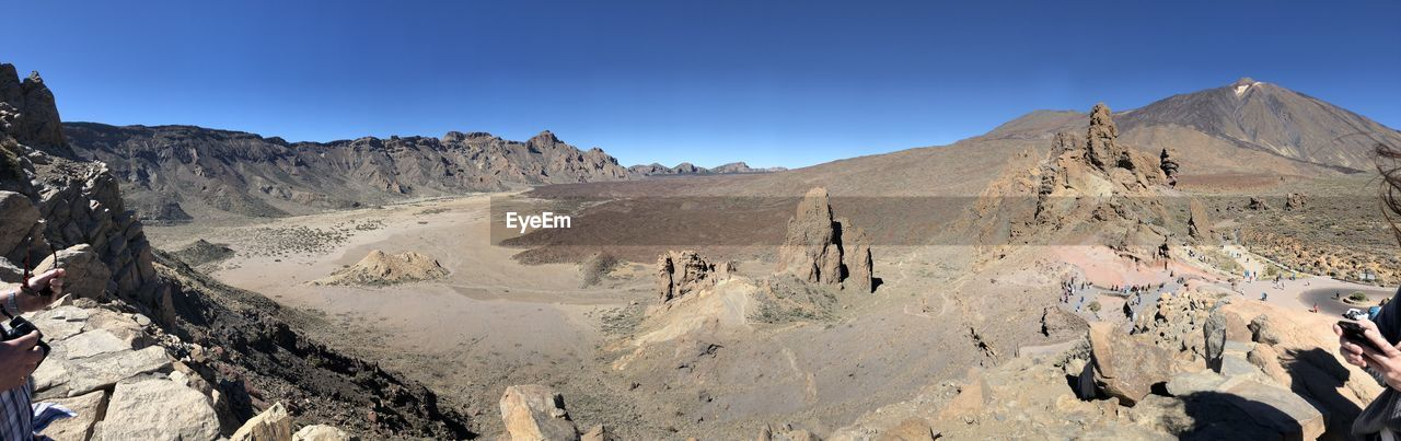 sky, mountain, scenics - nature, tranquil scene, landscape, beauty in nature, tranquility, environment, nature, clear sky, non-urban scene, mountain range, rock, rock formation, sunlight, day, remote, blue, rock - object, idyllic, arid climate, no people, climate, outdoors, formation, eroded