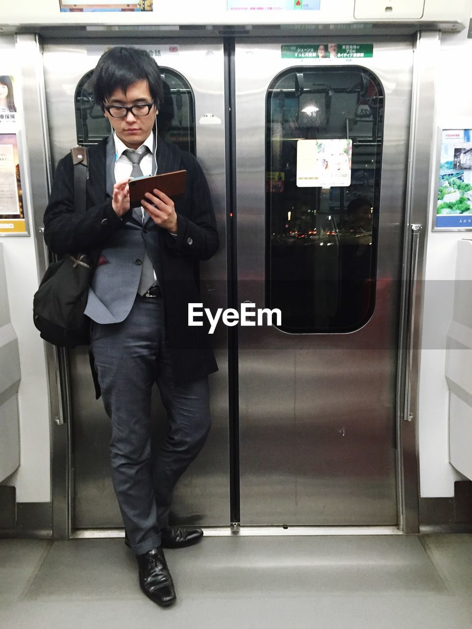 wireless technology, technology, real people, communication, portable information device, indoors, smart phone, mobile phone, standing, transportation, front view, connection, one person, holding, full length, lifestyles, young adult, day, people