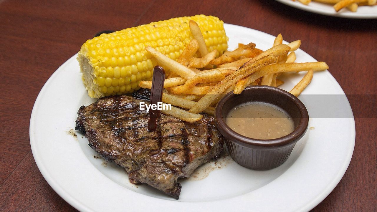 Close-up steak served with corn and fries