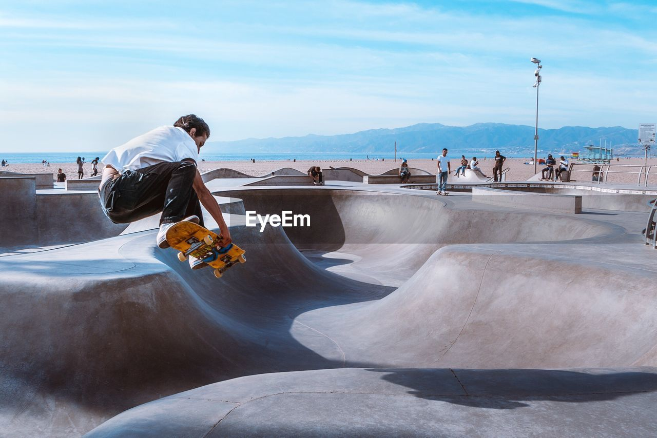real people, sky, leisure activity, day, men, motion, outdoors, one person, lifestyles, nature, skill, skateboard park, beauty in nature, water, stunt, full length, adventure, sea, people
