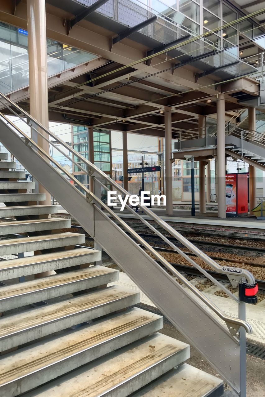 architecture, rail transportation, indoors, track, built structure, transportation, public transportation, no people, railroad track, metal, staircase, railroad station, railing, day, railroad station platform, mode of transportation, connection, technology, steps and staircases, ceiling