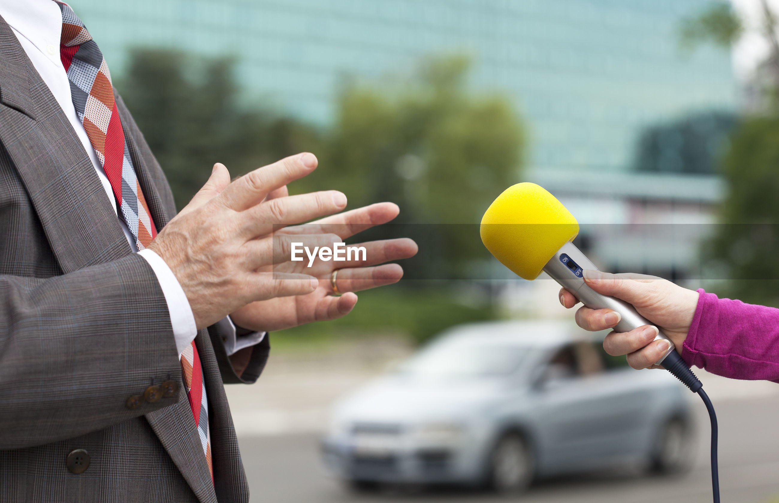 Cropped hand of reporter interviewing businessmen