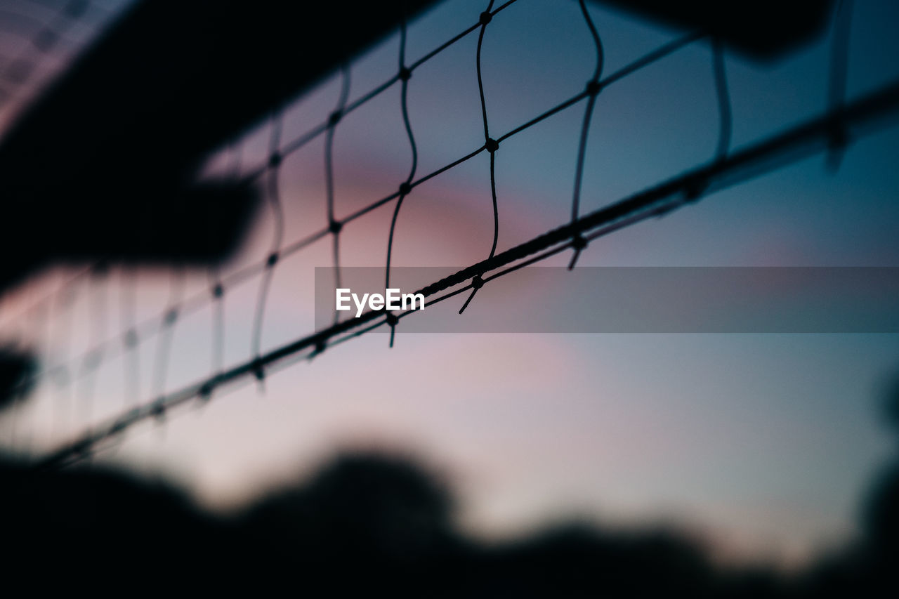Close-Up Of Silhouette Net Against Sky At Sunset
