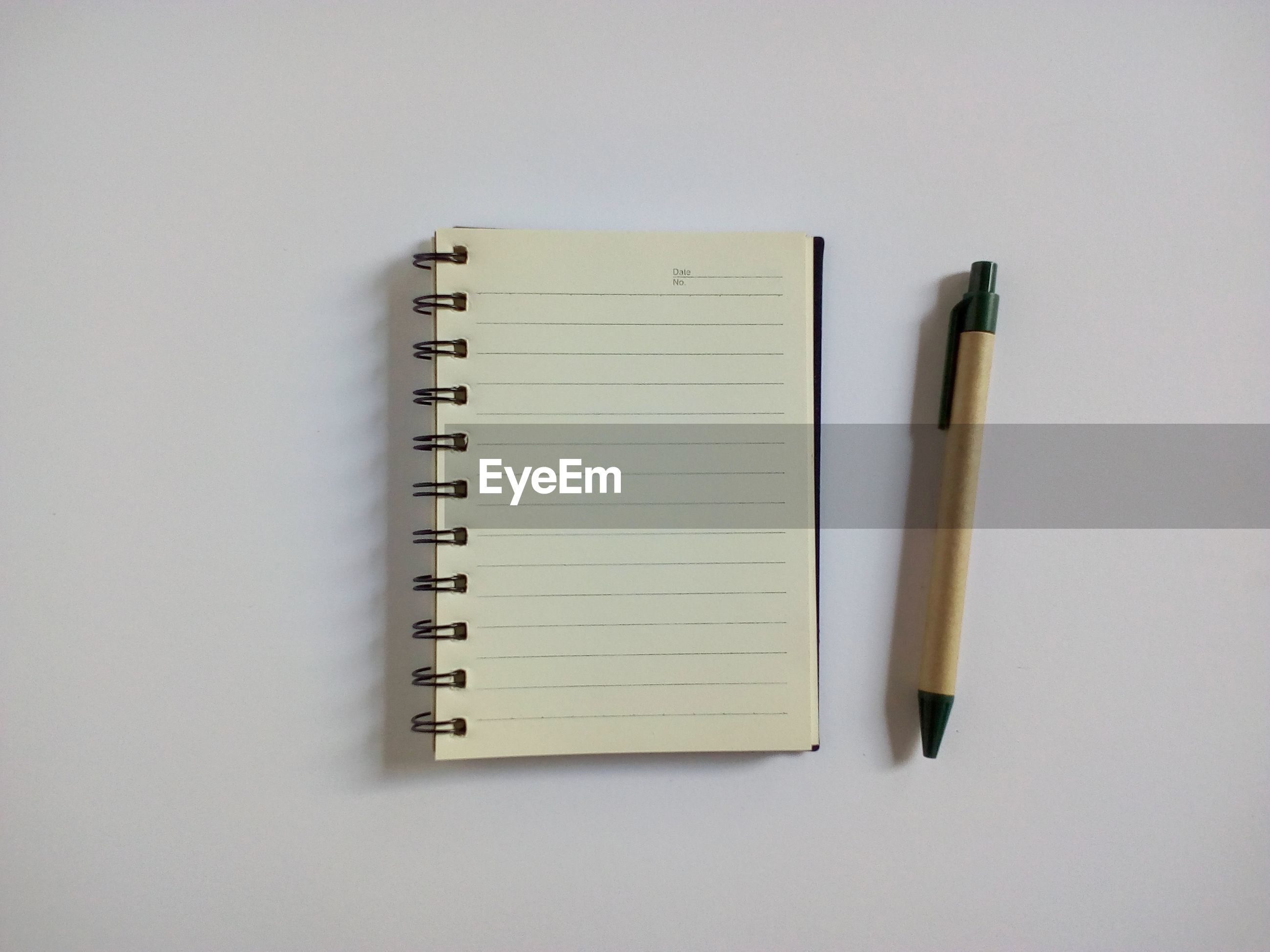 Directly above shot of spiral notebook with pen on table