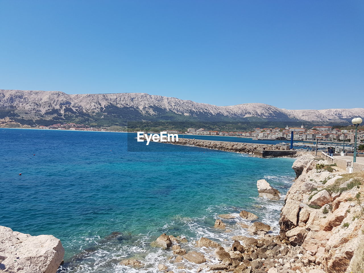 nature, clear sky, copy space, day, rock - object, outdoors, blue, water, beauty in nature, scenics, tranquil scene, mountain, tranquility, sea, sunlight, no people, sky