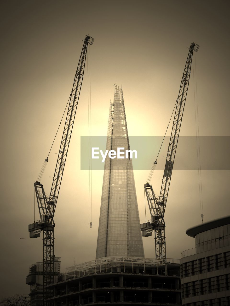 Low Angle View Of Cranes With Shard London Bridge Against Clear Sky