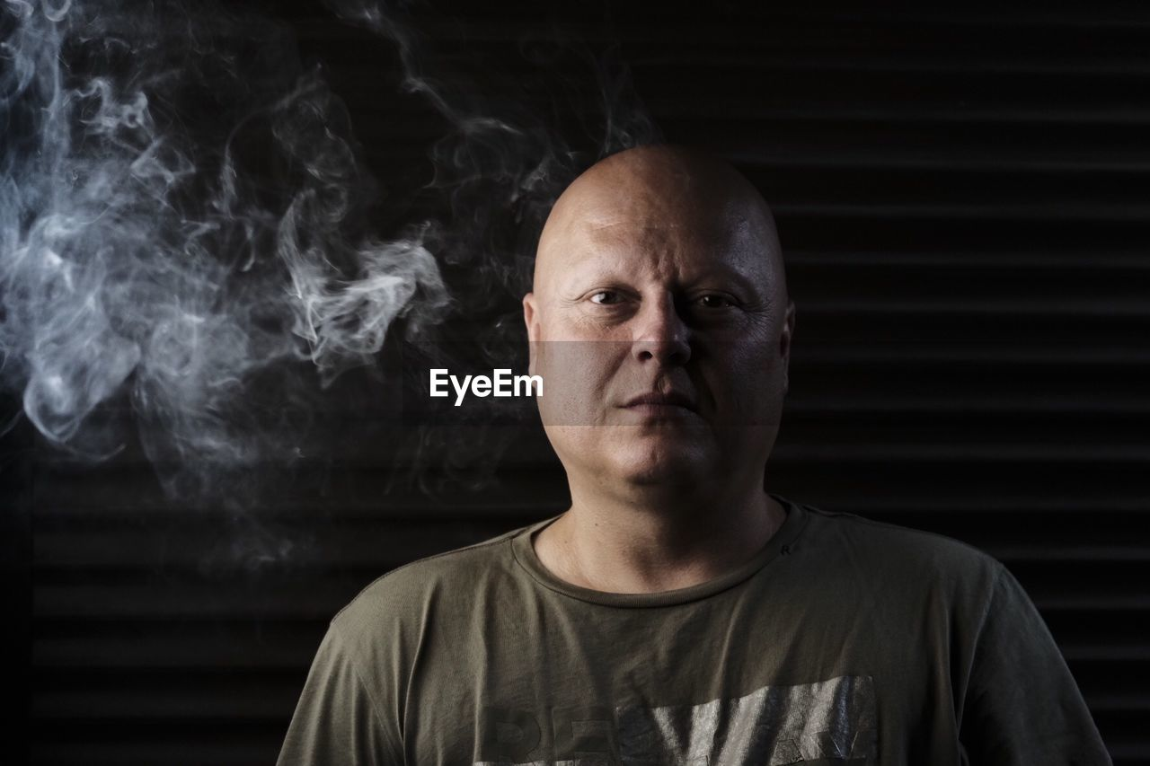 portrait, one person, headshot, looking at camera, front view, smoke - physical structure, real people, indoors, lifestyles, males, casual clothing, men, smoking issues, mid adult men, social issues, mid adult, adult, mature men