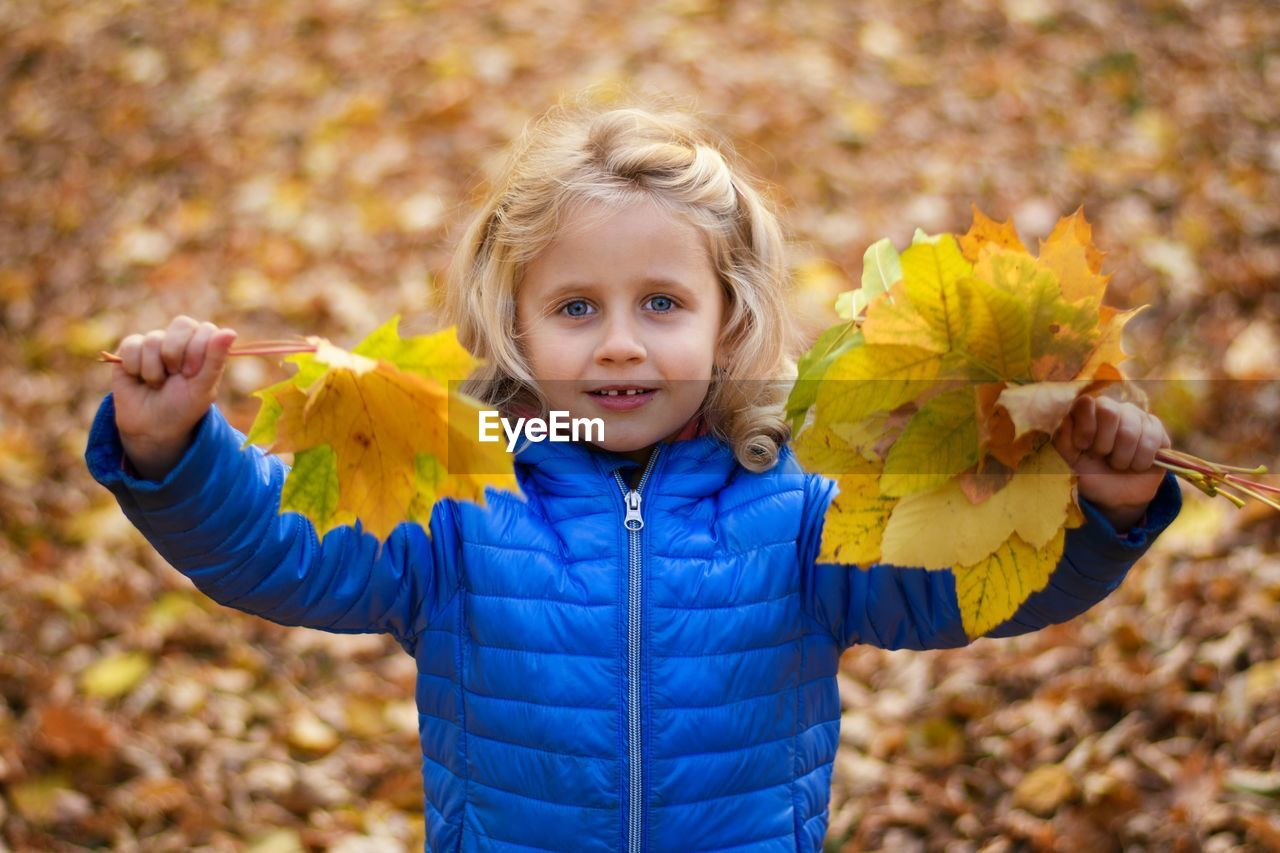 Portrait of smiling girl with autumn leaves standing on field