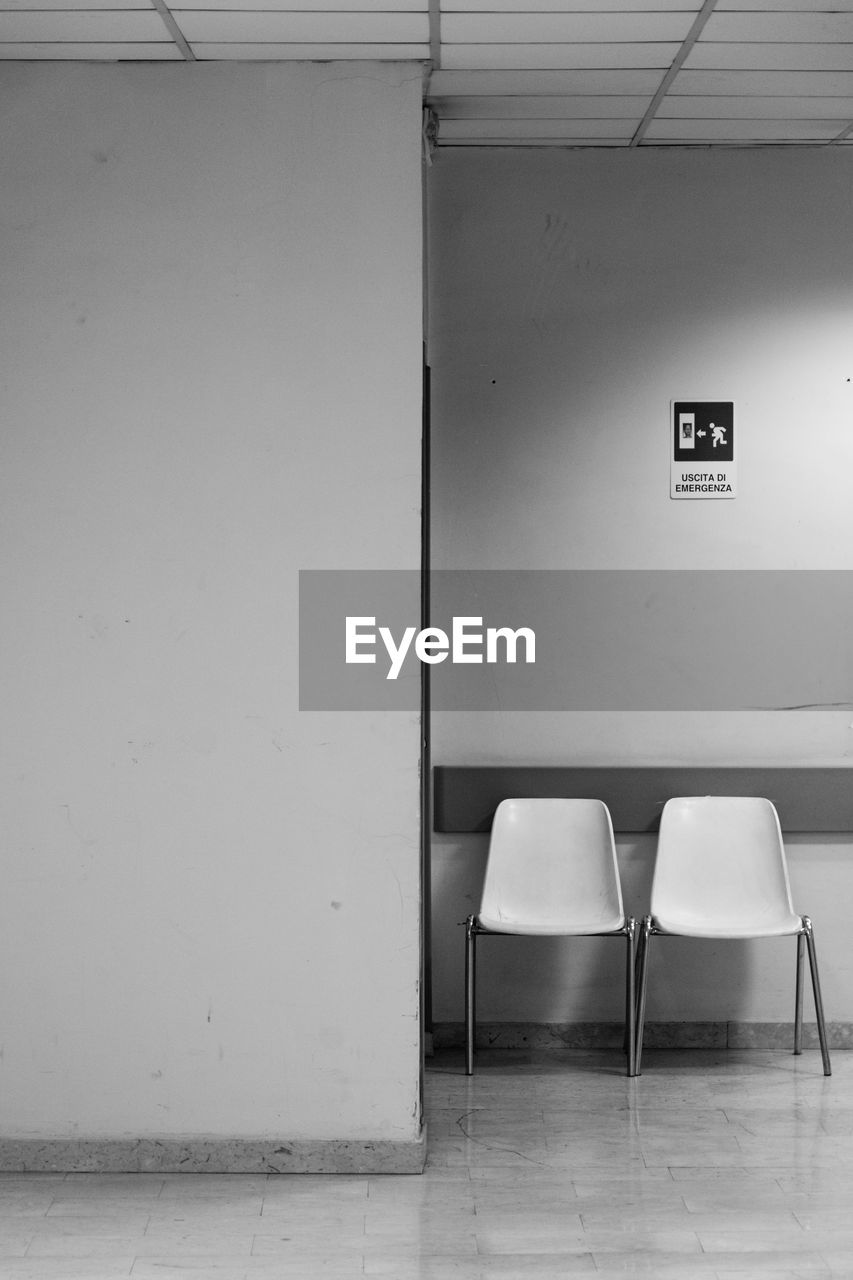 seat, wall - building feature, chair, absence, empty, indoors, architecture, no people, flooring, built structure, wall, building, door, sign, copy space, communication, entrance, white color, domestic room, day