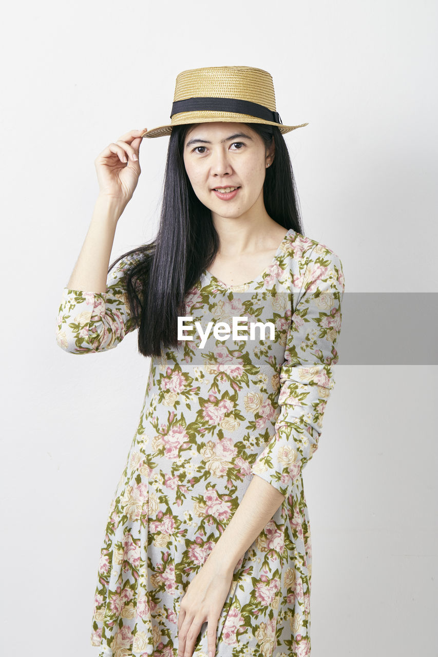 young women, young adult, one person, hat, studio shot, front view, indoors, leisure activity, looking at camera, hair, standing, clothing, portrait, white background, long hair, lifestyles, hairstyle, three quarter length, beautiful woman, casual clothing, fashion, teenager, floral pattern