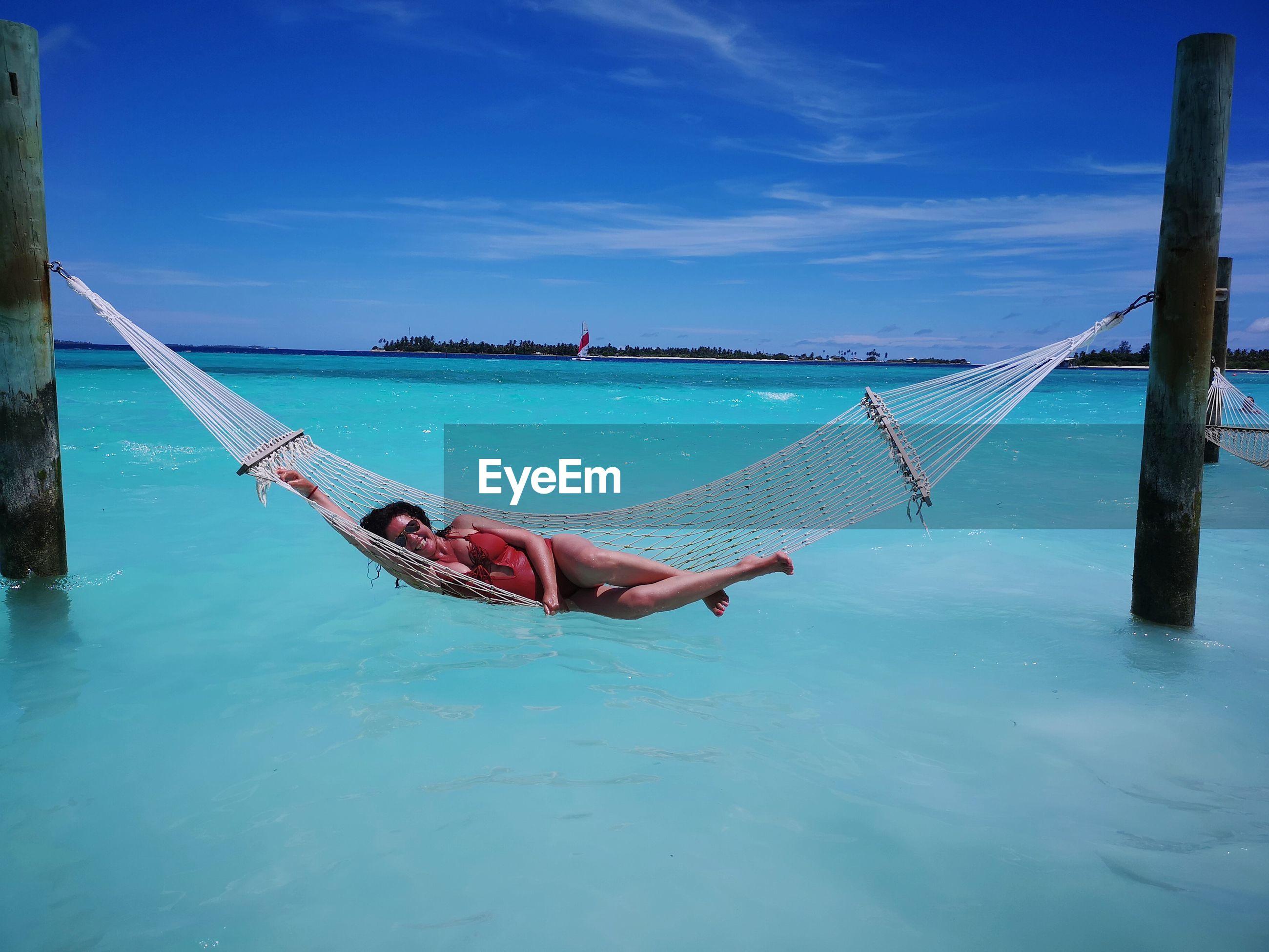 Woman lying on hammock over sea