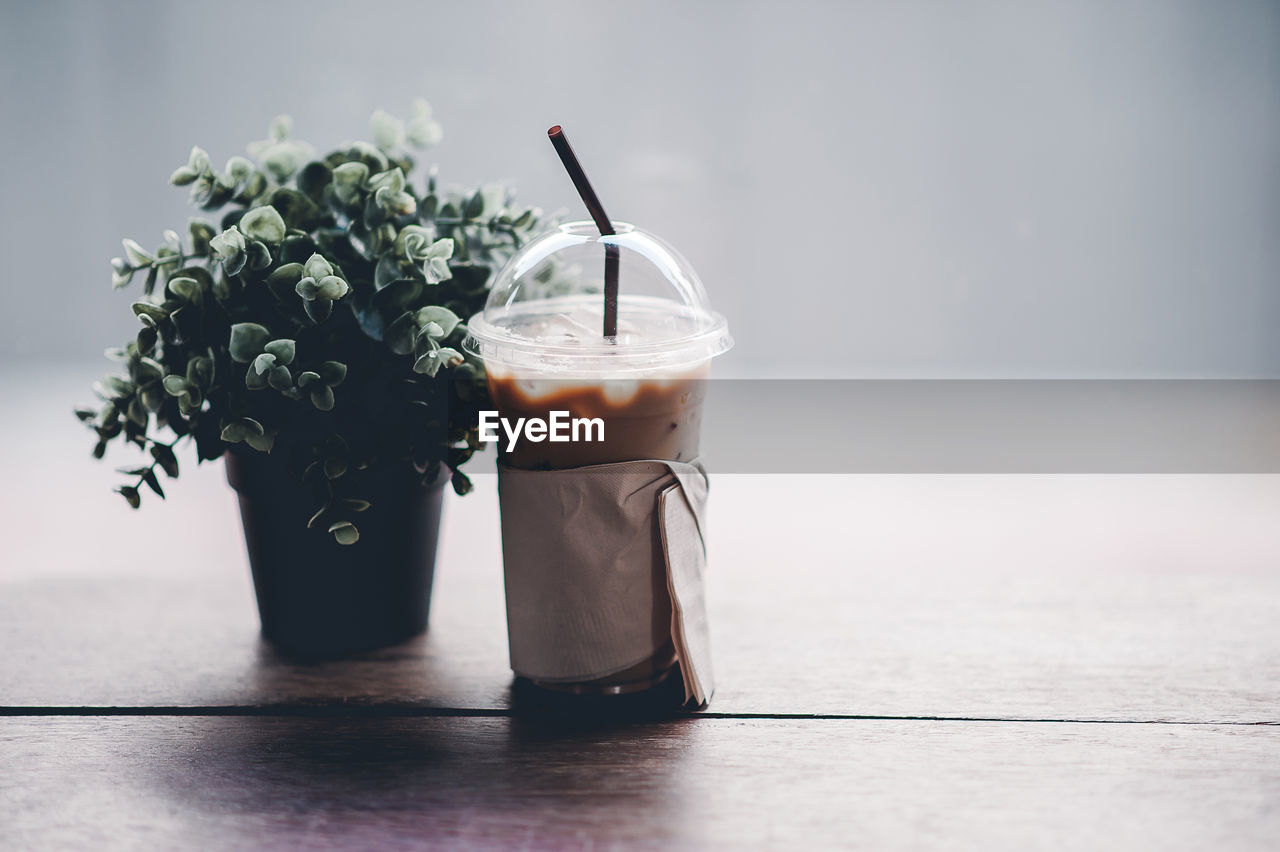 table, food and drink, drink, freshness, food, indoors, still life, no people, refreshment, glass - material, close-up, glass, drinking straw, straw, focus on foreground, selective focus, drinking glass, household equipment, wood - material, healthy eating