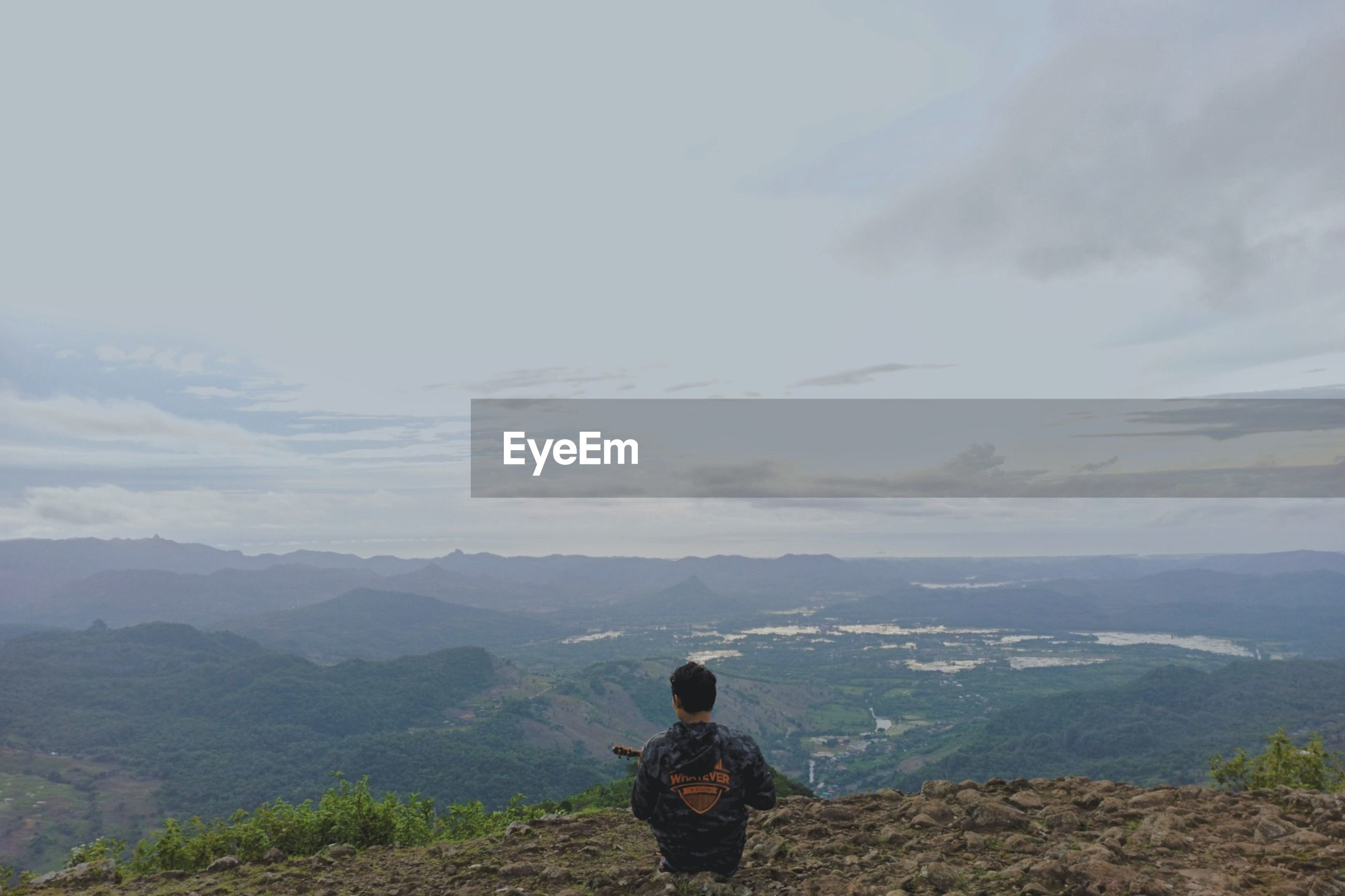 REAR VIEW OF PERSON STANDING ON MOUNTAIN