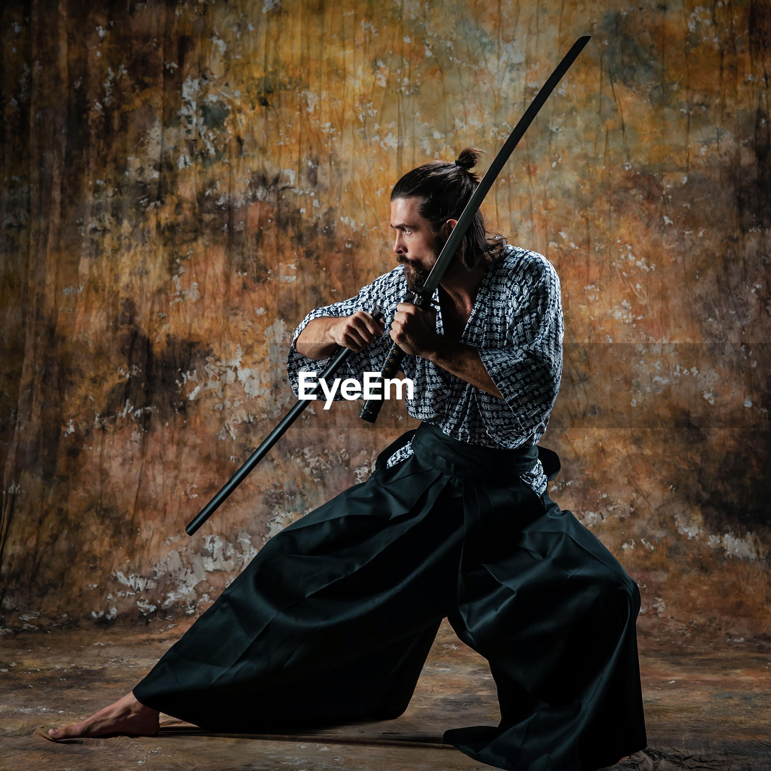 Full length of man practicing ninja against wall