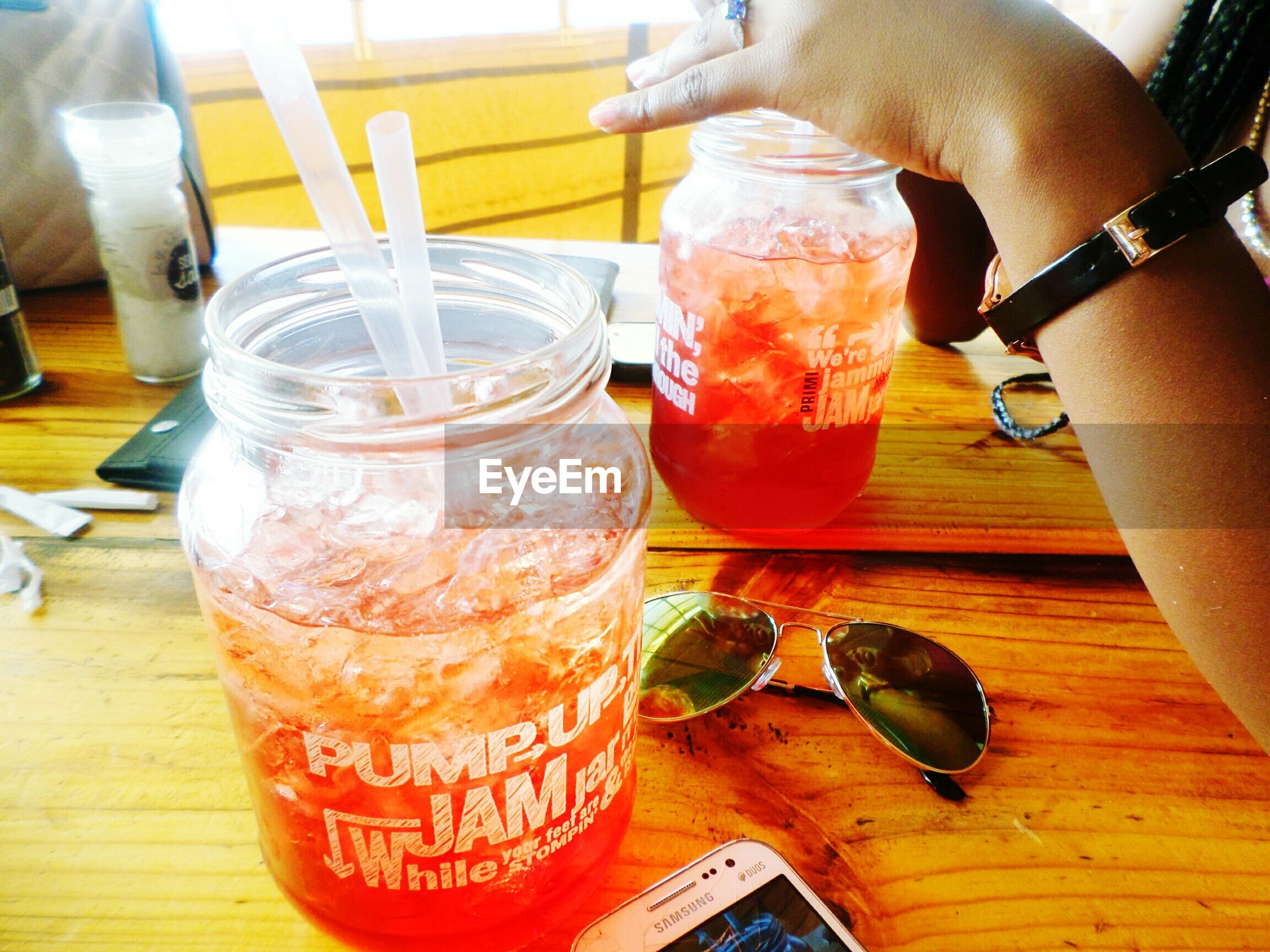 food and drink, drink, table, drinking glass, refreshment, freshness, indoors, person, alcohol, wood - material, lifestyles, holding, drinking straw, restaurant, close-up, leisure activity, cocktail