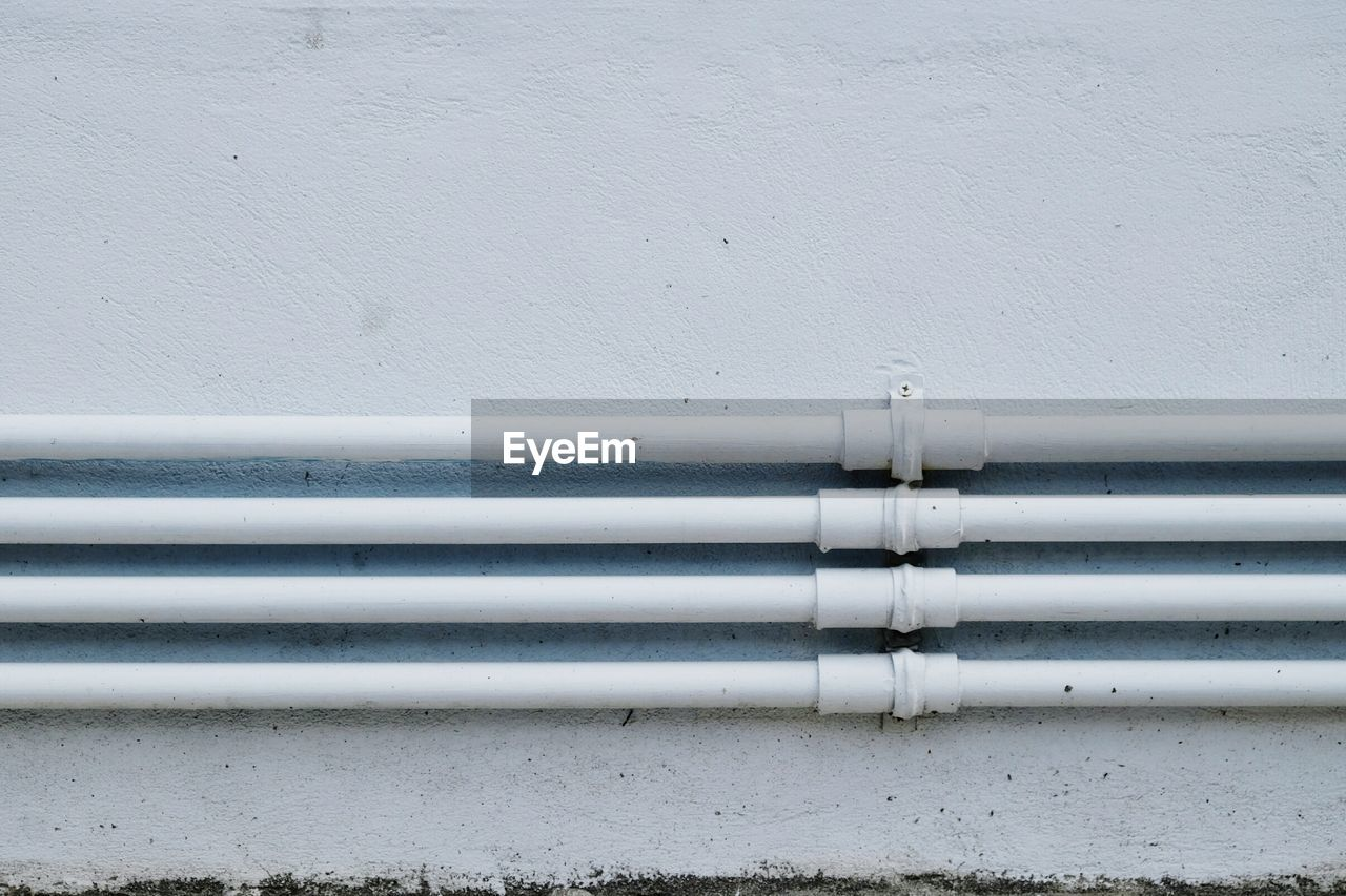 CLOSE-UP OF WHITE PIPE ON METAL STRUCTURE
