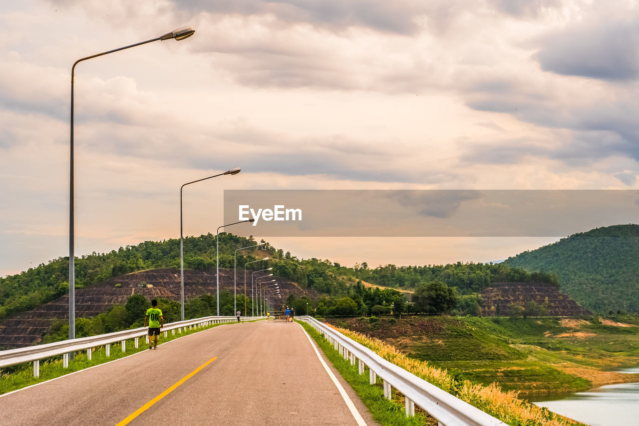 road, cloud - sky, sky, transportation, the way forward, direction, street light, street, nature, plant, sign, tree, scenics - nature, beauty in nature, symbol, no people, road marking, marking, non-urban scene, lighting equipment, diminishing perspective, outdoors