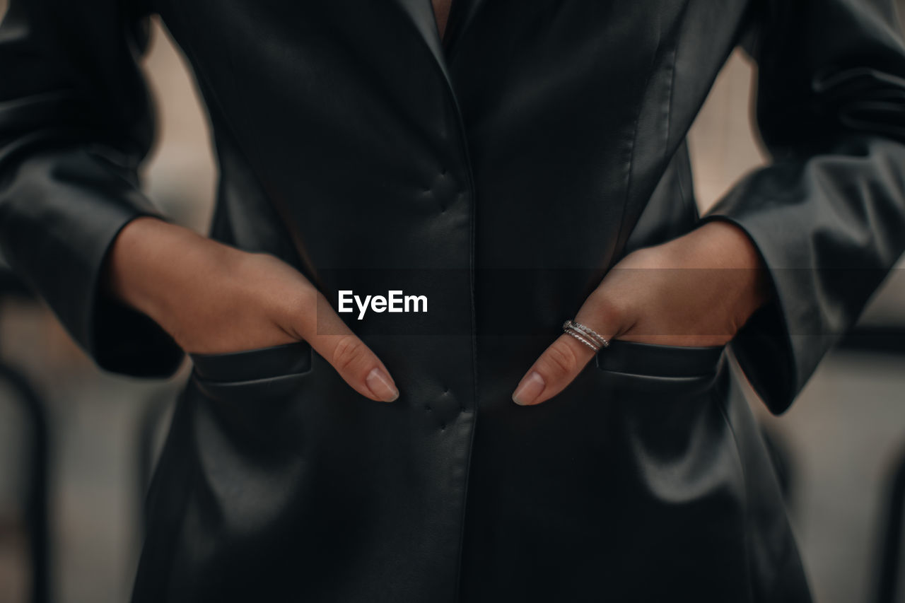 Female hands with silver rings in the pockets of a black long leather jacket. jewelry