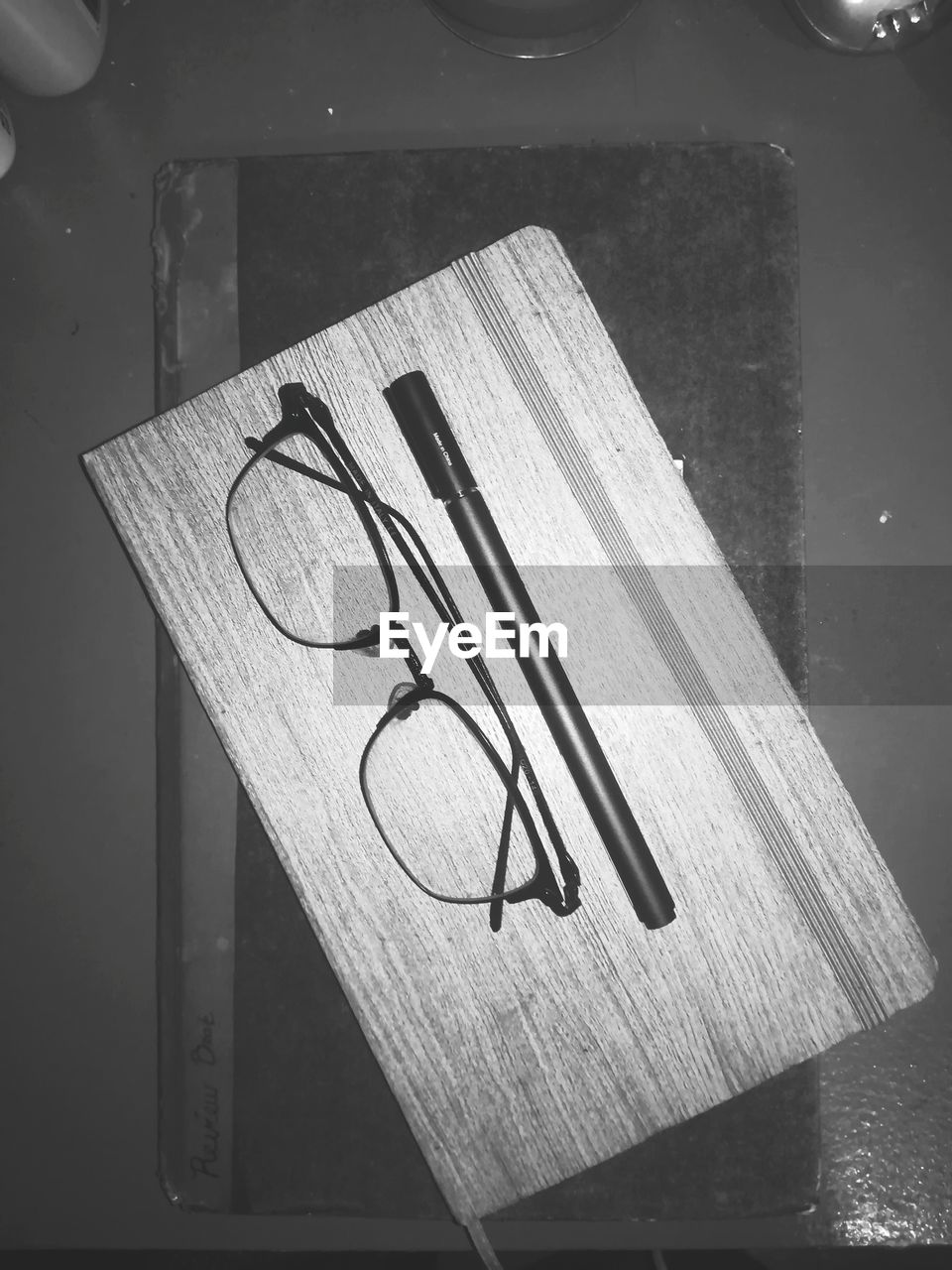 no people, table, indoors, eyeglasses, still life, close-up, high angle view, glasses, paper, wood - material, art and craft, book, creativity, shape, glass - material, publication, geometric shape, pencil, wireless technology, napkin