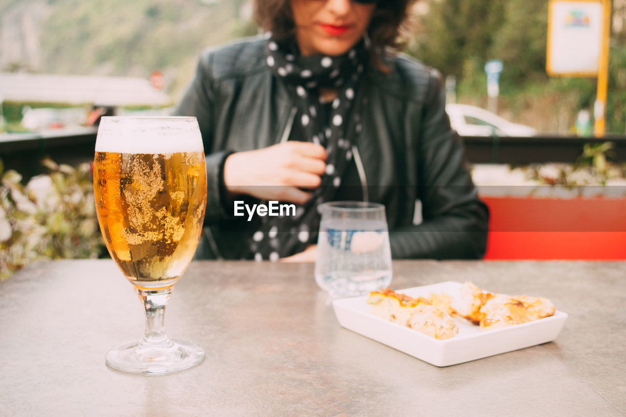 Mid adult woman sitting by beer glass on table
