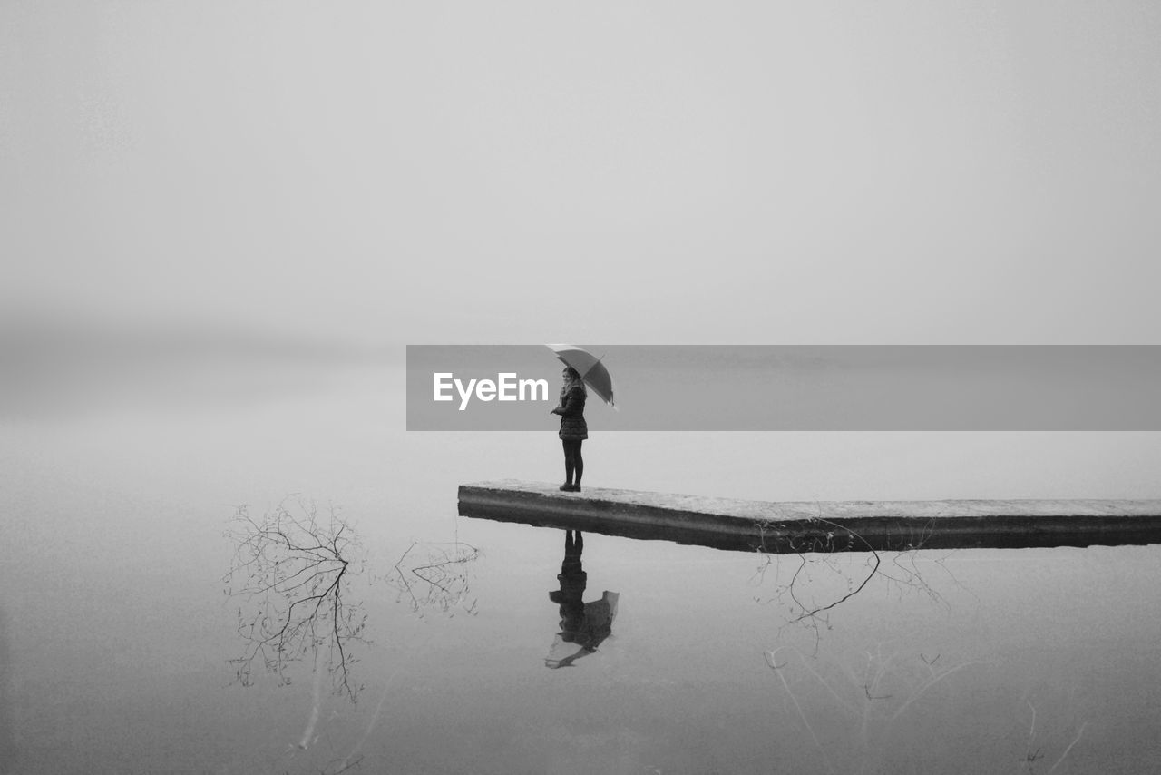 water, reflection, lake, waterfront, one person, sky, scenics - nature, tranquility, tranquil scene, nature, beauty in nature, full length, standing, day, copy space, fog, real people, non-urban scene, outdoors