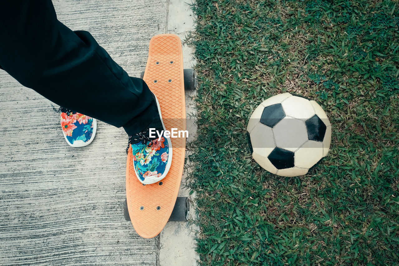 Low Section Of Man With Surfboard By Soccer Ball On Grassy Field