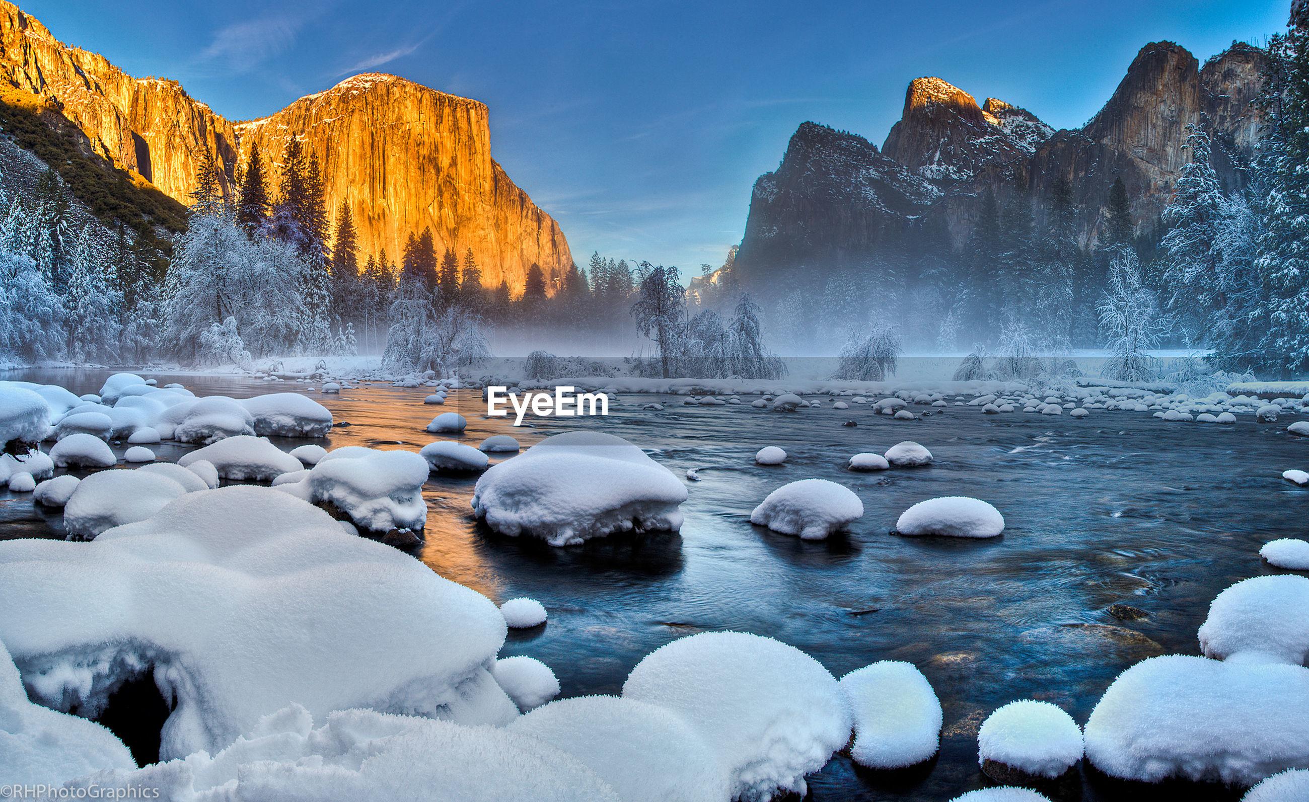 Calm lake against rocky mountain range during winter