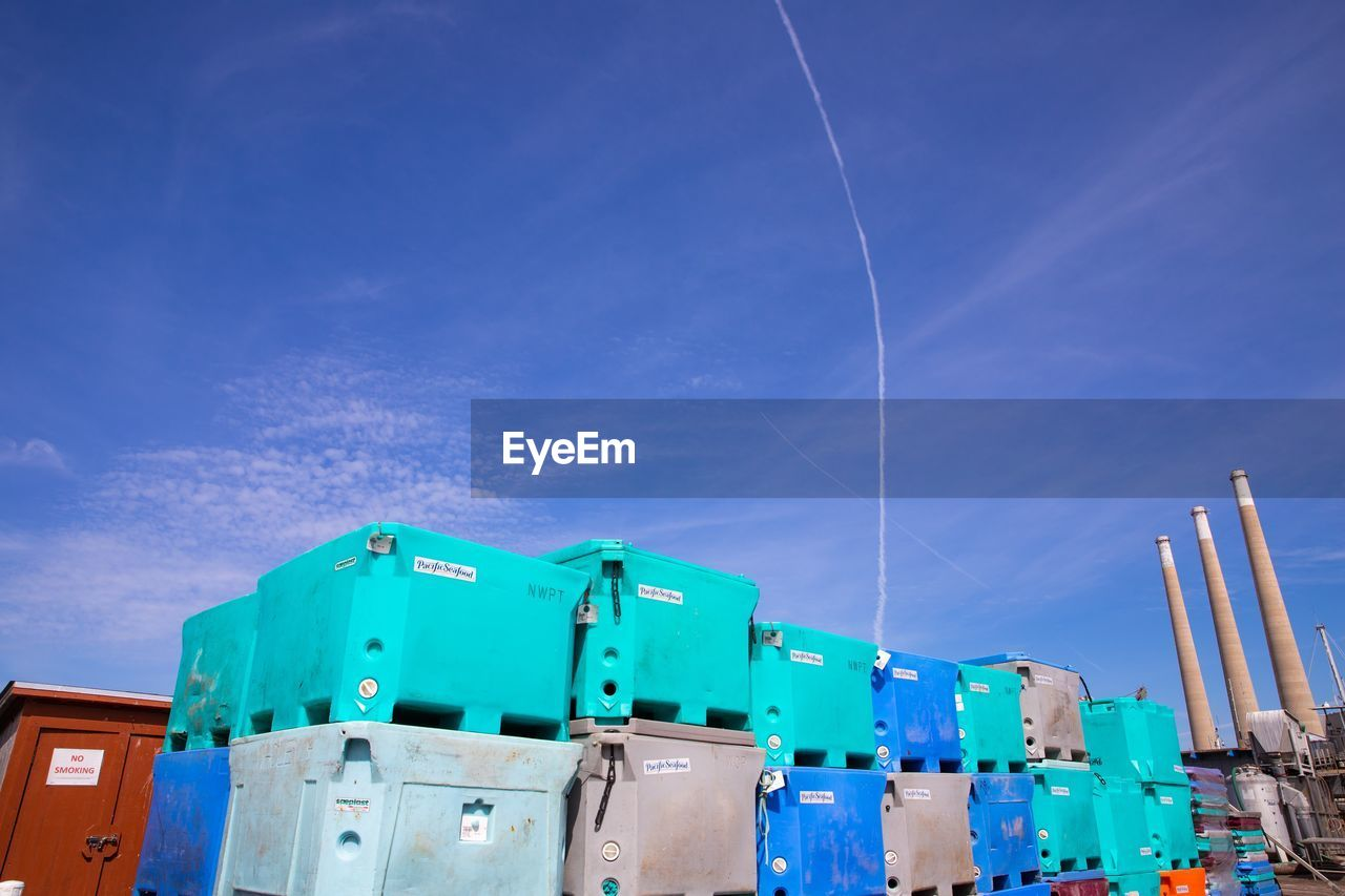 sky, blue, low angle view, nature, no people, cloud - sky, day, built structure, vapor trail, outdoors, architecture, building exterior, sunlight, container, metal, plastic, industry, multi colored, fuel and power generation, technology