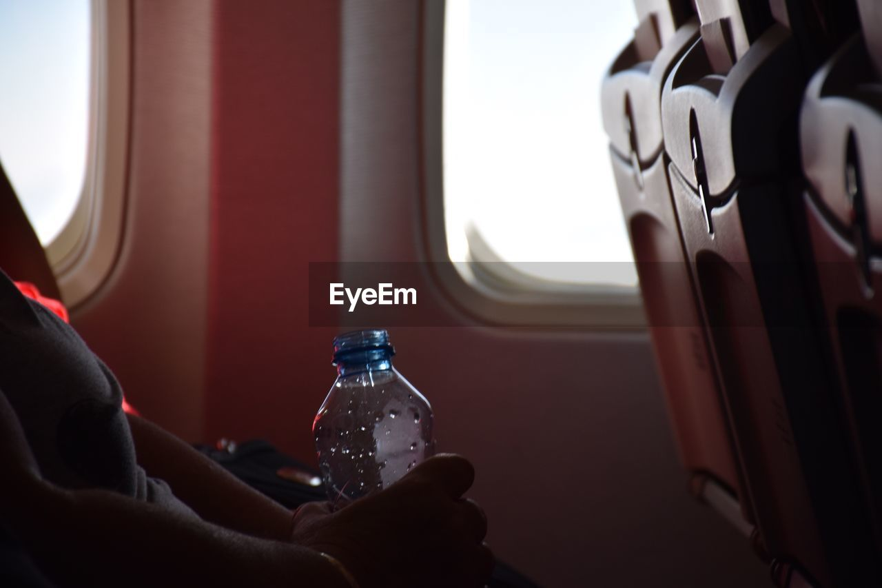 Midsection Of Woman With Water Bottle Sitting In Airplane