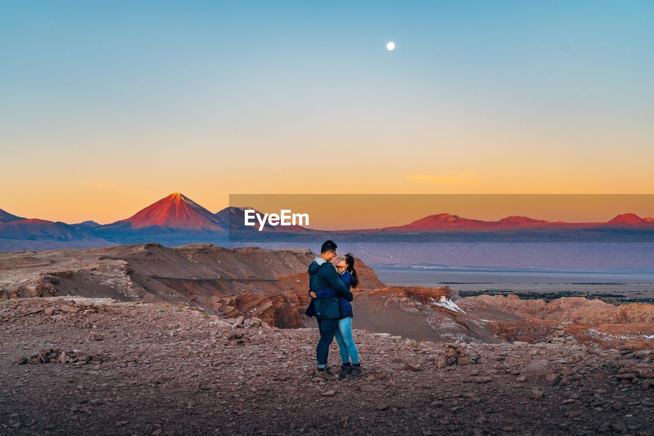 Couple Embracing While Standing On Mountain Against Clear Sky During Sunset