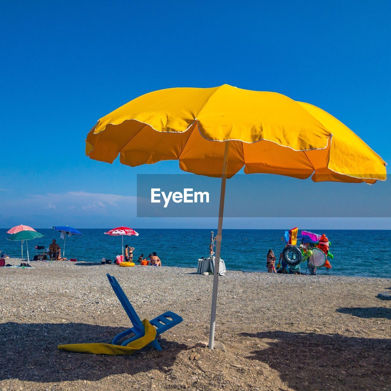 water, sea, beach, land, sky, parasol, protection, shade, umbrella, sand, nature, beach umbrella, blue, sunlight, yellow, clear sky, horizon over water, day, beauty in nature, outdoors