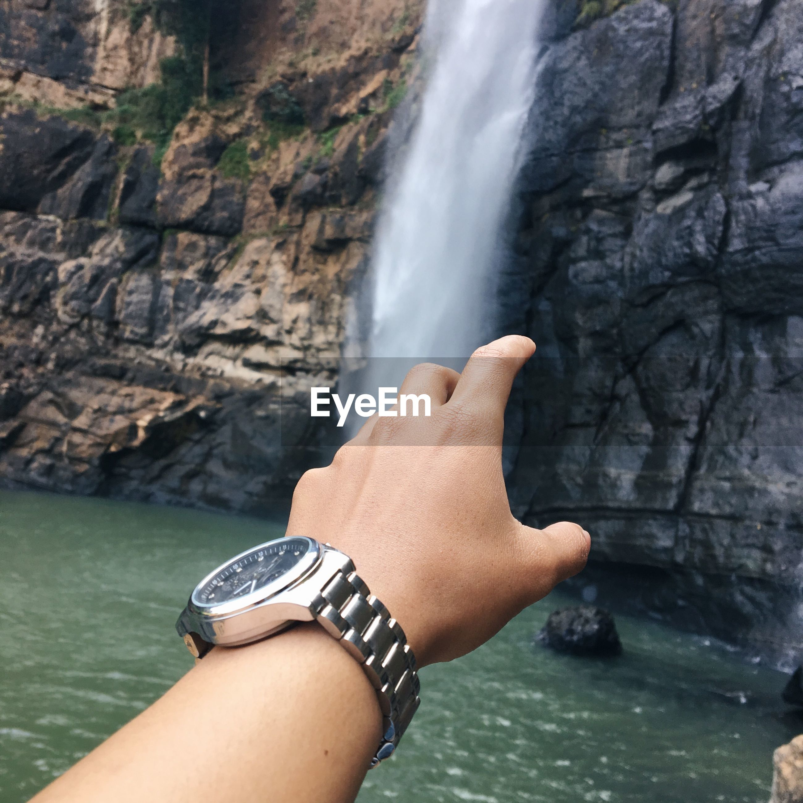 Cropped hand of man reaching waterfall