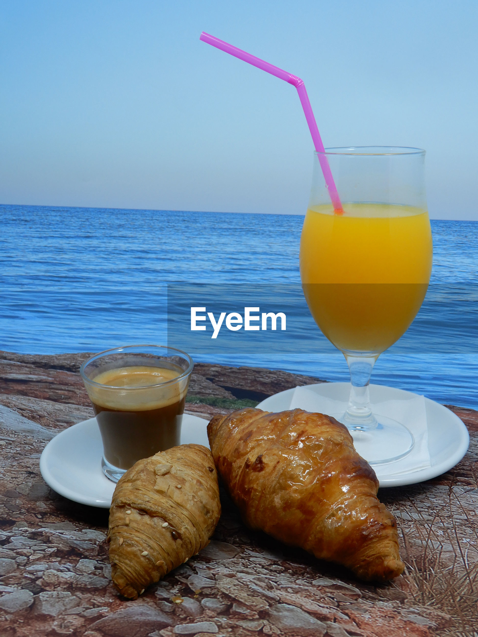 CLOSE-UP OF BREAKFAST ON TABLE AGAINST SEA