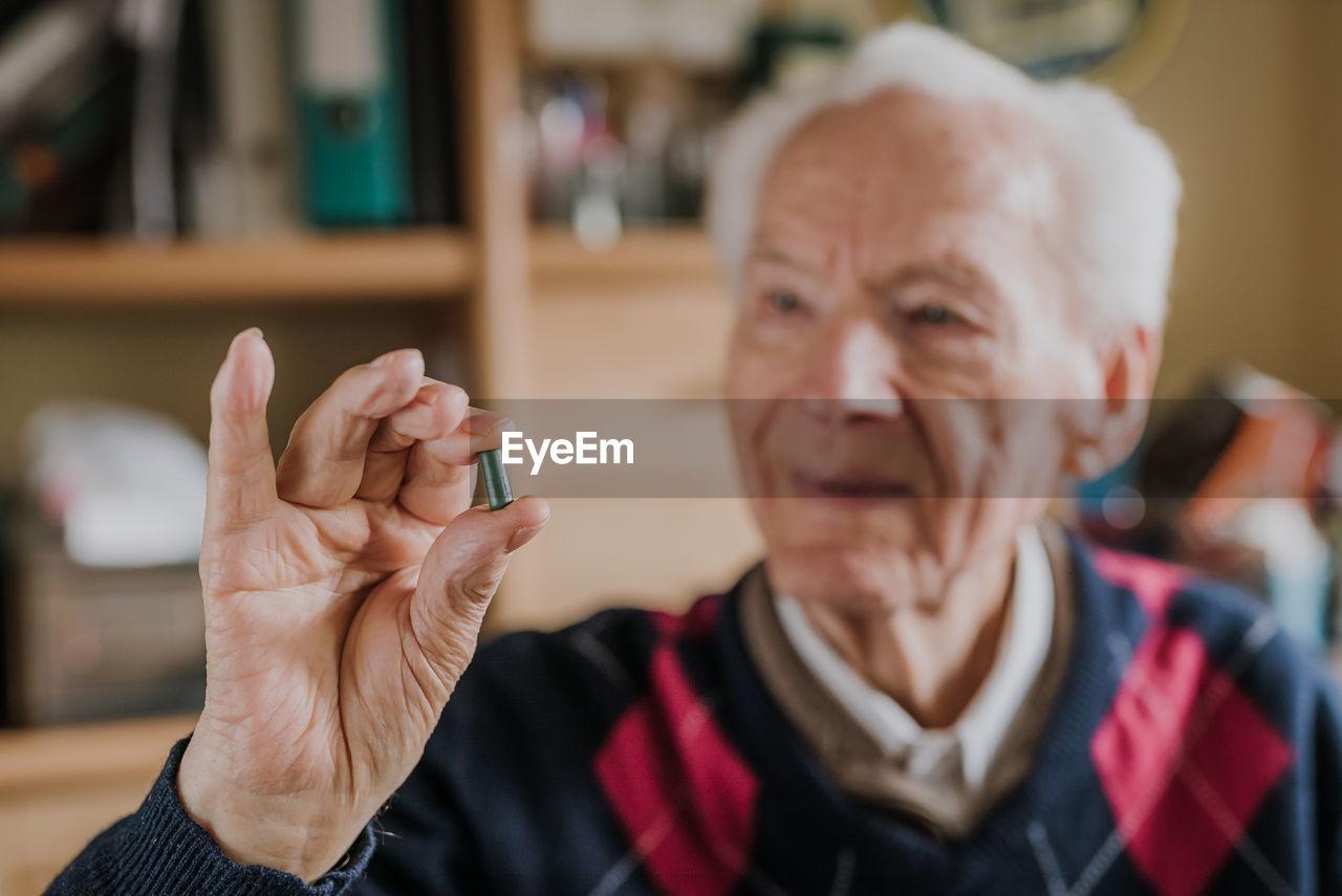 Smiling senior man holding capsule at home